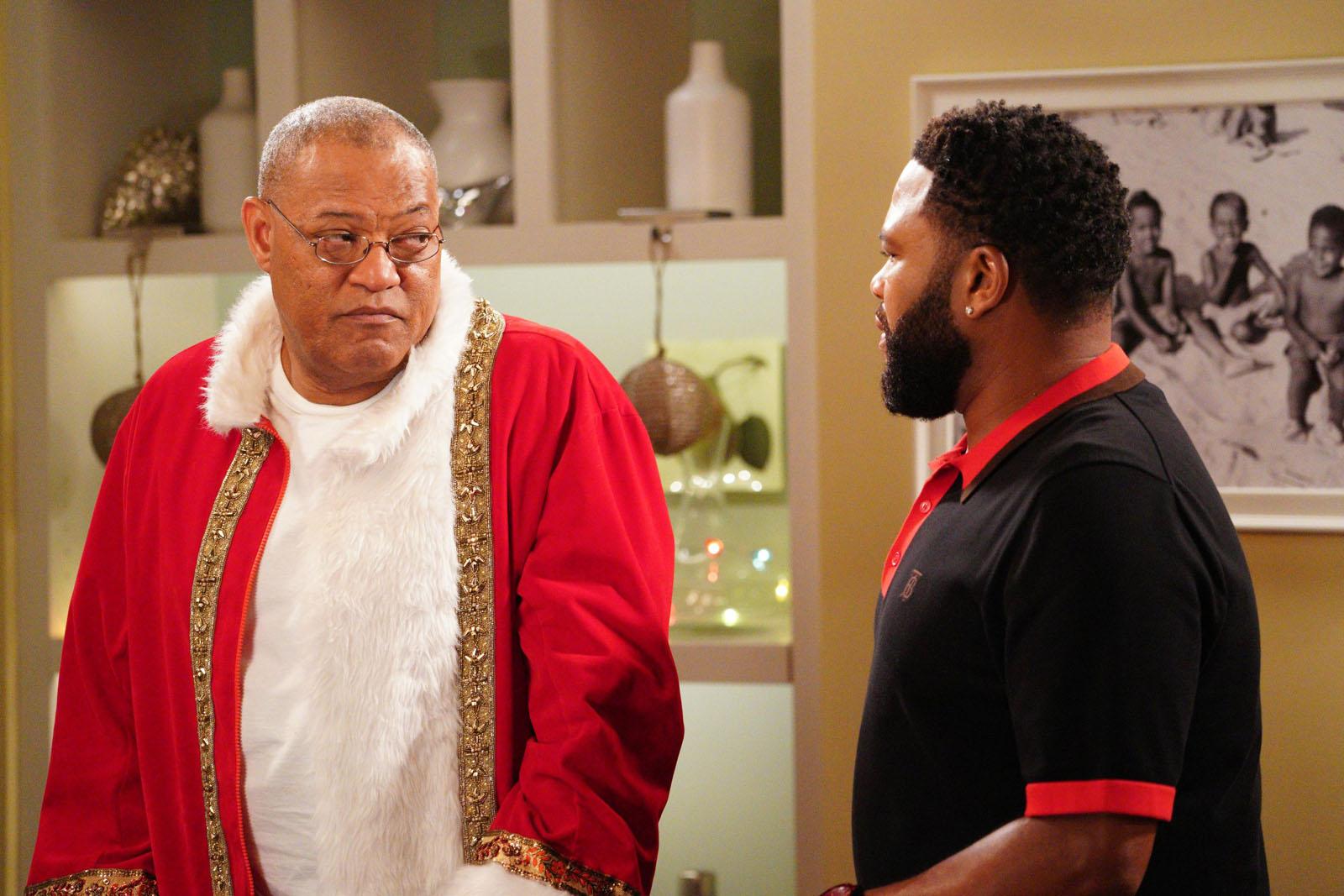 Cena de black-ish. Nela está um homem negro na esquerda vestindo fantasia de papai noel. Ele olha para sua direita, encarando o homem ao seu lado. Também negro, este veste uma blusa preta com detalhes em vermelho. No fundo está uma estante branca e um quadro preto e branco.