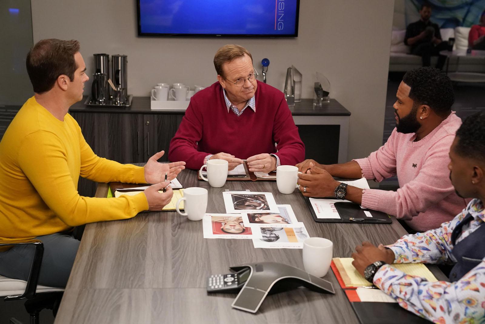 Cena de black-ish. Nela está um homem branco de blusa vinho sentado na ponta de uma mesa. A sua direita estão dois homens negros olhando para ele, com as mãos apoiadas na mesa em sua frente. Do outro lado, na esquerda, um outro homem branco, de blusa amarela e calça cinza, está também olhando para o homem central. No fundo há uma Tv e um balcão encostados em uma parede branca.