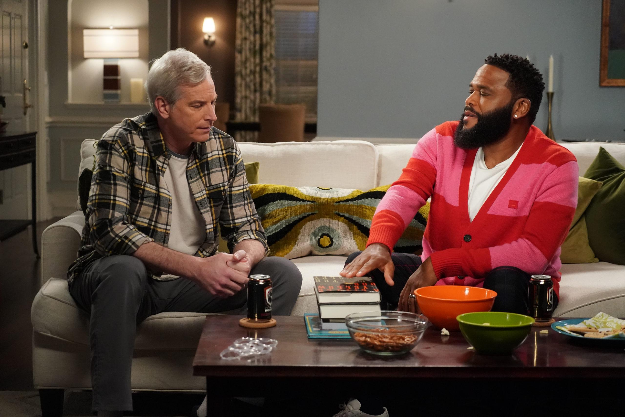 Cena de black-ish. Nela está dois homens sentados em um sofá branco com almofadas verdes. O da esquerda é branco, de cabelo cinza, e veste uma calça jeans junto a uma blusa branca com uma camisa xadrez verde por cima. Ao seu lado, na direita, o homem é negro e usa blusa listrada rosa e vermelho. Em sua frente está uma mesa de madeira escura com bebidas, comidas e livros, onde o homem da direita apoia a mão.