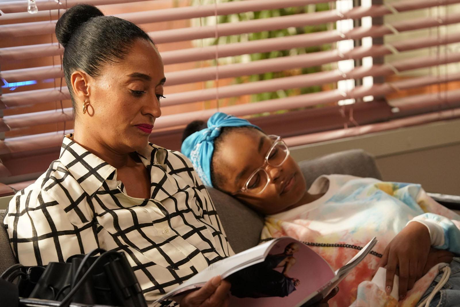 Cena de black-ish. Nela está uma mulher negra de blusa branca e preta listrada e cabelo preso lendo uma revista de capa rosa, sentada em um sofá cinza. A sua esquerda, também no sofá está uma garota negra com um pano azul na cabeça e blusa branca com manchas coloridas.