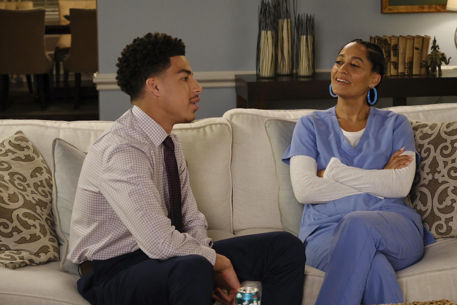 Cena de black-ish. Nela está um garoto e uma mulher sentados em um sofá branco. Na esquerda o jovem é negro e usa camisa listrada com uma gravata escura e calça social escura. Na direita, a mulher é negra e veste uniforme hospitalar azul.