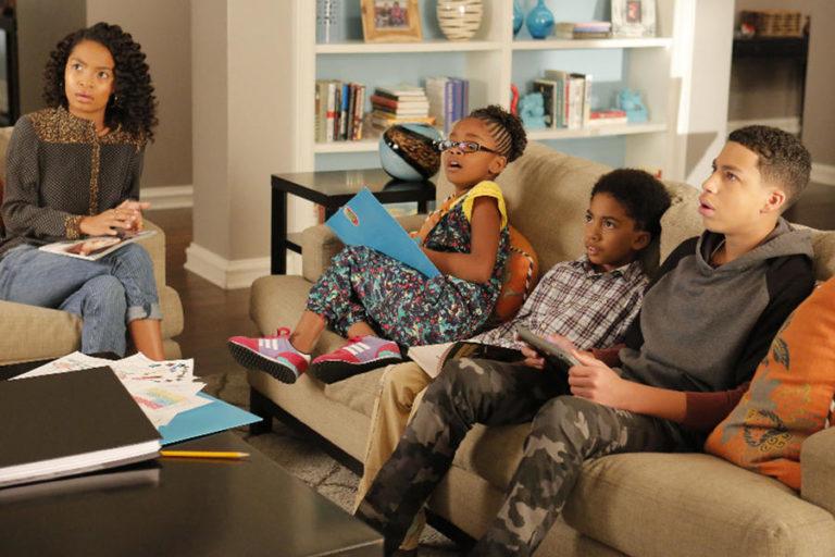 Cena de black-ish. Nela estão quatro jovens negros, duas garotas e dois meninos, olhando para frente com expressões assustadas. Todos sentam em um sofá bege, exceto pela menina na esquerda que está em um banco separado. No fundo há uma estante branca e na frente uma mesa de madeira escura com materiais espalhados sobre.
