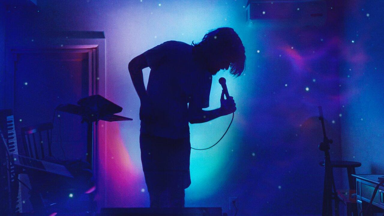 Cena do especial Bo Burnham: Inside. A foto mostra uma silhueta de Bo Burnham inclinado para a direita e com um microfone em mãos. Ele se encontra em um quarto com alguns objetos espalhados como um teclado,um suporte de microfone, um banquinho, e um notebook. O quarto é inteiramente banhado por uma projeção de um céu azul com estrelas.