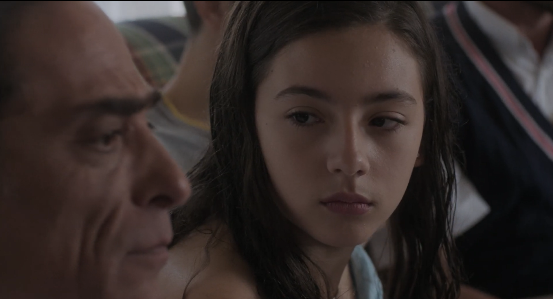 Cena do curta Brasil x Holanda. A cena mostra o foco no rosto de uma garota jovem e branca, de cabelos pretos, olhando diretamente para o rosto de um homem mais velho.