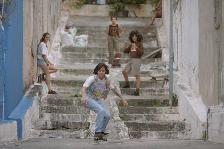 Cena do filme Meu Nome É Bagdá. Na imagem, vemos uma escadaria. Ao lado esquerdo, vemos uma das personagens do filme encostada na parede. Ao fundo no centro, vemos duas das personagens com seus skates e observando outra personagem, em primeiro plano ao centro, andando de skate.