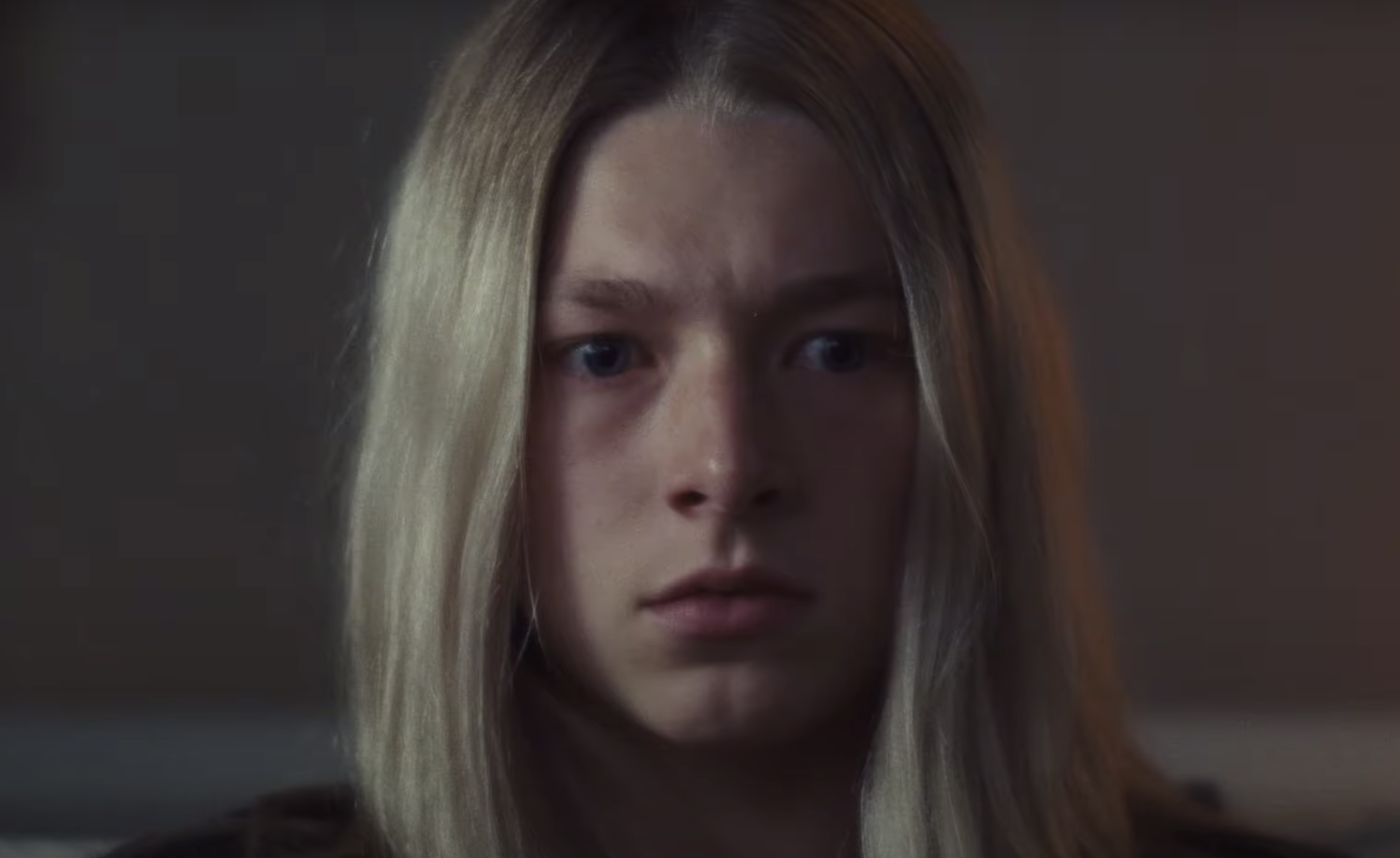 Cena da série Euphoria. Na imagem há o rosto da personagem Jules. Ela é uma mulher branca de cabelos loiros e olhos azuis. Sua expressão mostra medo, confusão e tristeza. O fundo da imagem é uma parede bege desfocada.