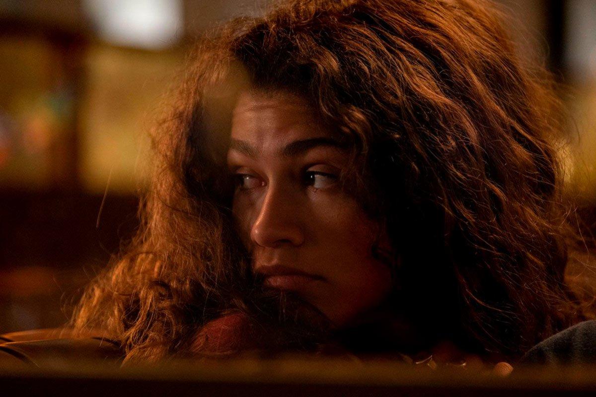 Cena da série Euphoria. Na imagem há o rosto da protagonista Rue. Ela é uma mulher negra de pele clara com cabelos castanhos cacheados bagunçados, está com o pescoço virado para o lado, os olhos arregalados e atentos e sua expressão é conturbada. O fundo é um embaçado de luzes amarelas.