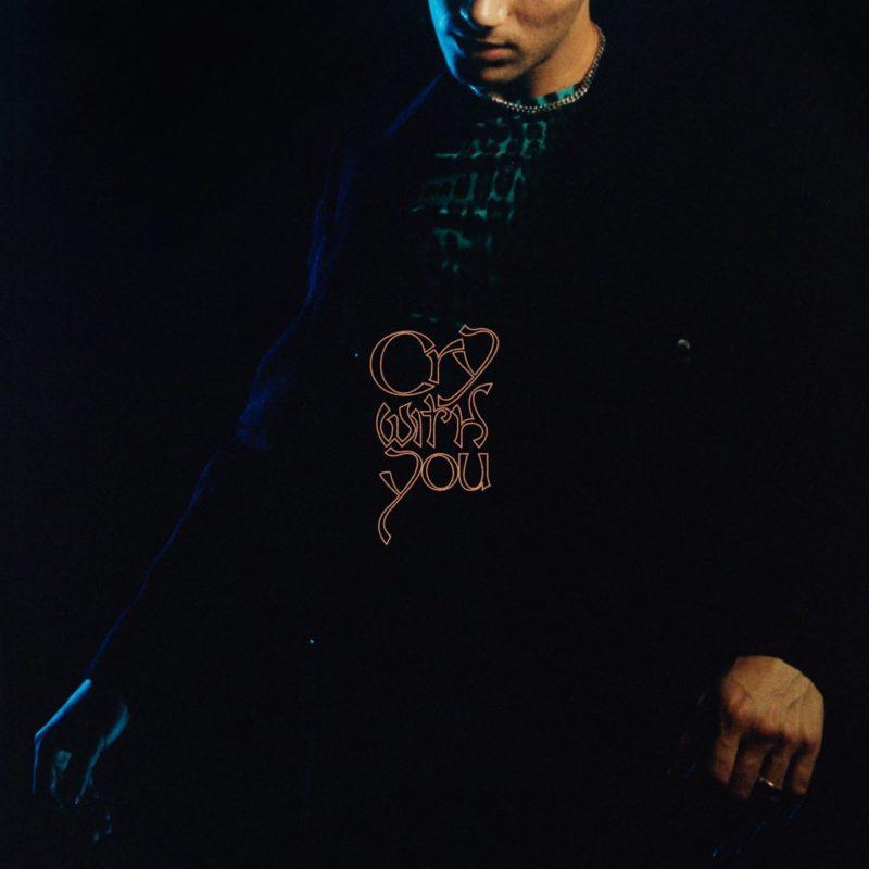 Capa de Cry With You, do Jeremy Zucker. A foto de metade do corpo do cantor mostra a parte de baixo de seu rosto, que é branco, e sua roupa escura, com uma blusa verde por trás da calça e jaqueta preta. No centro da imagem está o nome da música em bege.