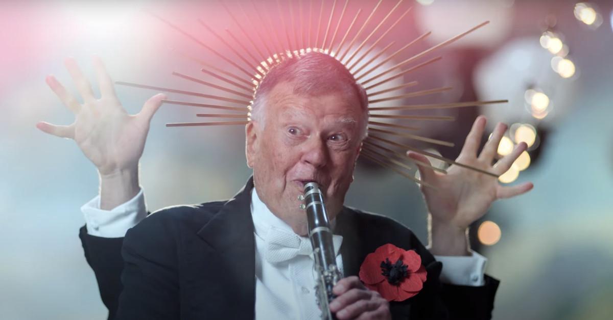 Cena de As Mortes de Dick Johnson. Vemos um homem idoso tocando uma flauta. Ele veste terno com uma rosa de papel na lapela. Há várias linhas douradas ao redor de sua cabeça, como se ele fosse uma figura religiosa. Atrás dele, vemos dois braços levantados, mostrando a palma das mãos. O fundo está desfocado, com um brilho de várias cores