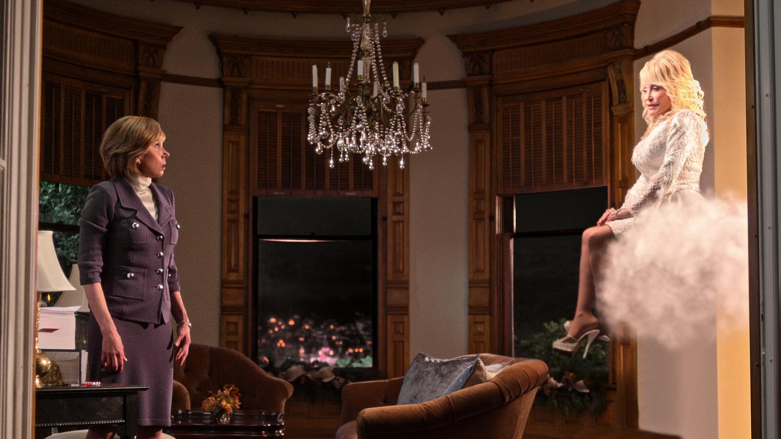 Cena do filme Natal com Dolly Parton. A cena mostra a personagem de Christine Baranski, uma mulher branca e idosa, usando terninho cinza e olhando para um anjo iluminado. O anjo é Dolly Parton, uma idosa branca, loira e usando roupas angelicais.