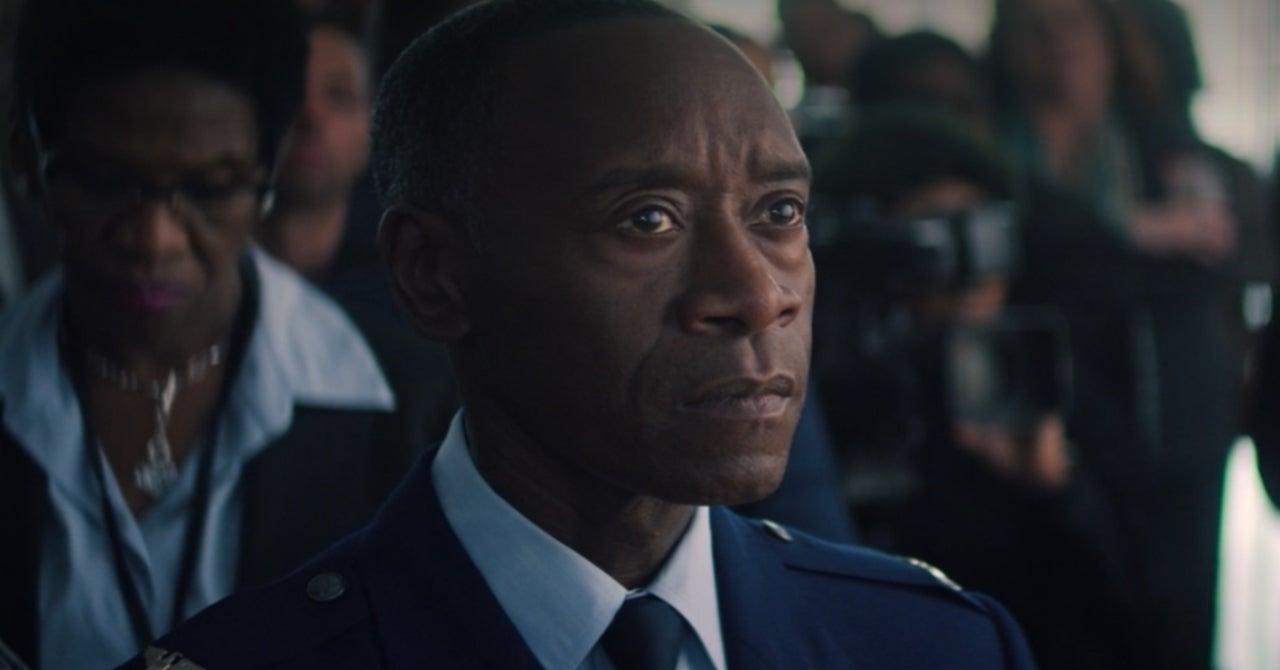 Cena da série Falcão e o Soldado Invernal. A cena mostra Rhodes, personagem de Don Cheadle, olhando para algo em um close-up. Ele é um homem idoso, negro e com cabelos raspados rente à cabeça. Ele usa um terno meio uniforme militar, com medalhas no peito, além de camisa branca e gravata escura.