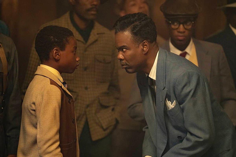 Cena da série Fargo. Na foto, Rodney L. Jones olha para Chris Rock, que interpretam Satchel Cannon e Loy Cannon, respectivamente. Rodney é um menino negro, com cabelo curto preto, e veste uma blusa de cor bege. Chris Rock é um homem negro, veste um terno azul, com lenço branco no bolso, e camisa branca com listras pretas. Ele possui um bigode grisalho e cabelo preto, penteado para o lado. Ele está flexionando levemente os joelhos para ficar na altura de Rodney.