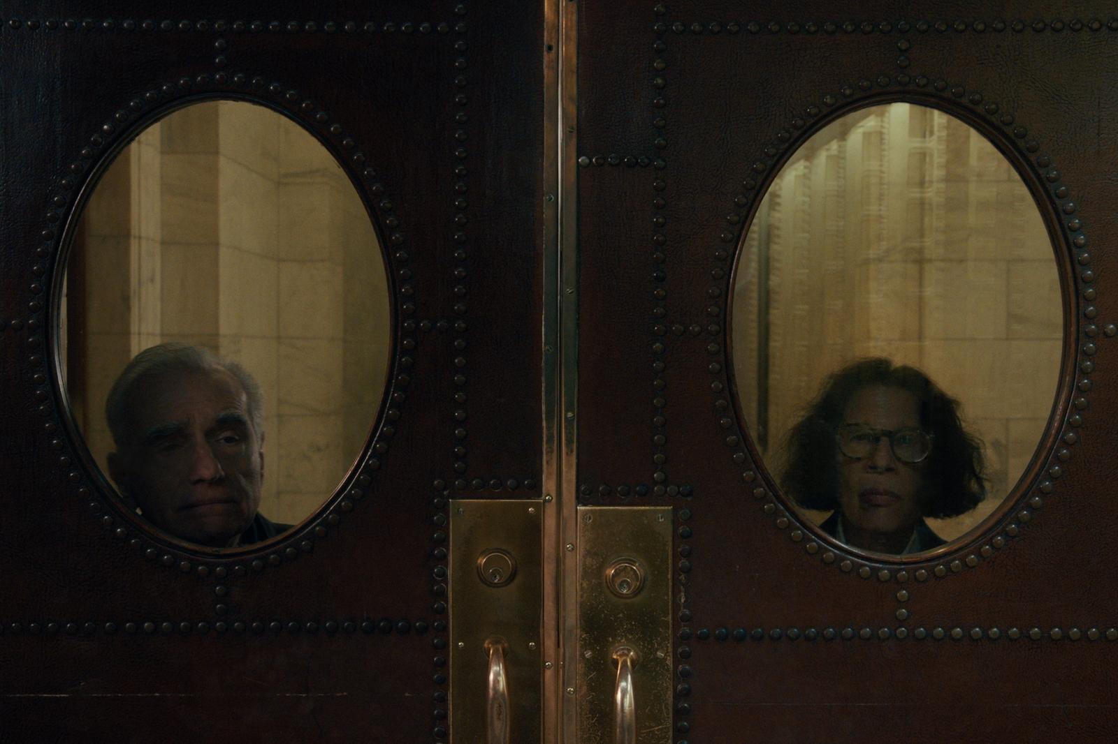 A imagem é uma cena de Faz de Conta que NY é uma Cidade. Nela, Martin Scorsese e Fran Lebowitz estão atrás de uma porta, com seus rostos posicionados em um vão em formato ovalado. Martin Scorsese é um senhor branco, de cabelos grisalhos; e Fran Lebowitz é uma senhora branca, de cabelos castanhos e curtos, ela usa óculos de grau.