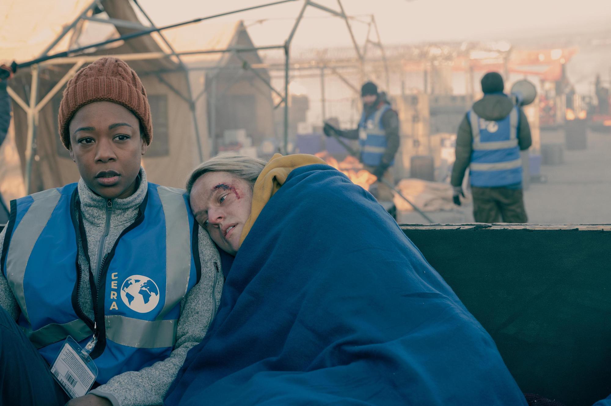 A imagem retangular é uma cena de The Handmaid's Tale. À esquerda há Samira Wiley, uma mulher negra e jovem e à sua direita há Elisabeth Moss, uma mulher branca, jovem, loira de cabelos curtos e bagunçados. Elas estão com roupas de ONGS, azul e uma manta da mesma cor. Elas estão em uma zona de guerra com diversas tendas e trabalhadores.