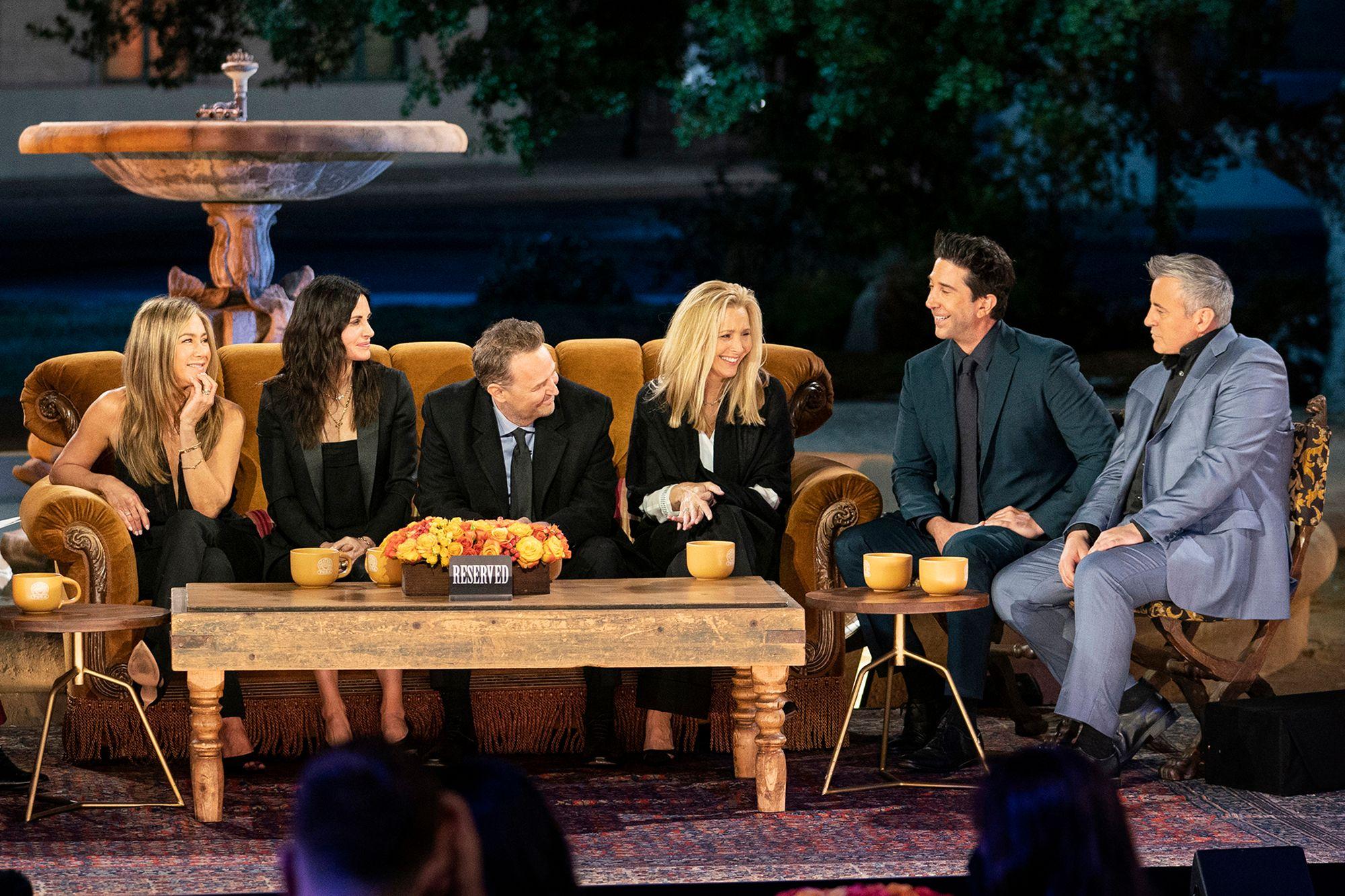 A imagem é uma cena do especial Friends: The Reunion. Nela, estão sentados em um sofá em frente a uma fonte de água, da esquerda para direita: Jennifer Aniston, Courteney Cox, Matthew Perry e Lisa Kudrow. David Schwimmer e Matt LeBlanc estão sentados em duas poltronas ao lado direito do sofá. Em frente ao sofá, há uma mesa de centro, com um vaso com flores, três canecas amarelas e uma placa escrito Reserved em cima.