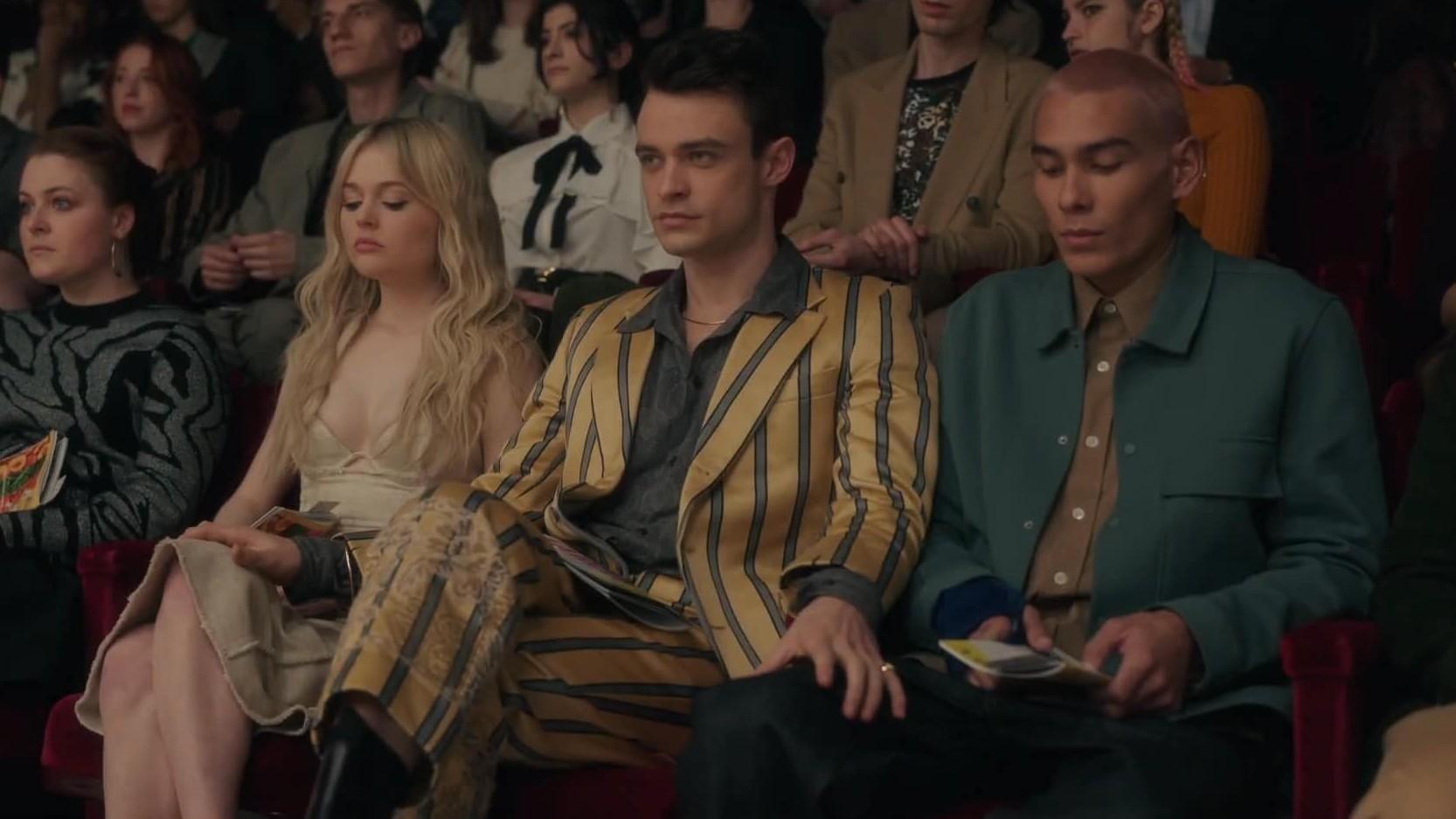 Cena da série Gossip Girl. A cena mostra o interior de um teatro, com 3 personagens sentados um ao lado do outro. À esquerda, está Audrey, branca e loira, ao meio está Max, branco e de cabelos pretos e terno amarelo, e à direita está Aki, asiático e de cabelo raspado rosa. Max está com as mãos nas coxas dos dois.