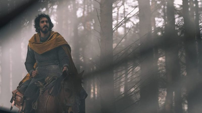 Cena do filme A Lenda do Cavaleiro Verde. Vemos um cavaleiro medieval andando a cavalo por uma floresta. O homem tem pele morena, barba cheia e cabelo preto grande. Veste uma malha cinza e tem um cachecol amarelo ao redor do pescoço.