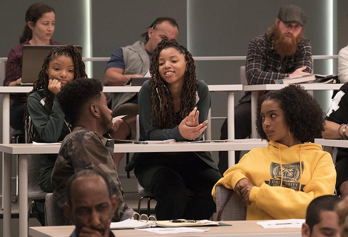 Cena de grown-ish. Nela está a foto de uma sala de aula com mesas brancas e paredes escuras. Centralizados estão quatro alunos: na frente, uma garota negra de cabelo cacheado usando uma jaqueta preta e um garoto negro de blusa militar olhando para atrás, aonde duas meninas negras usando a mesma blusa verde e mesmo estilo de penteado estão sentadas.