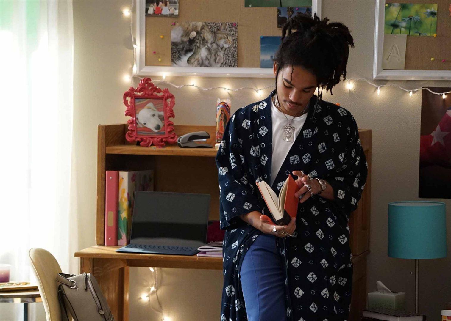 Cena de grown-ish. Nela está um garoto negro de cabelo estilo dread preso em cima da cabeça. Ele usa um quimono azul estampado por cima de uma blusa branca e calça jeans. Segurando um livro de capa laranja, o menino está encostado em uma mesinha. No fundo há diversos materiais escolares e uma parede decorada por fotos e luzes pisca pisca.
