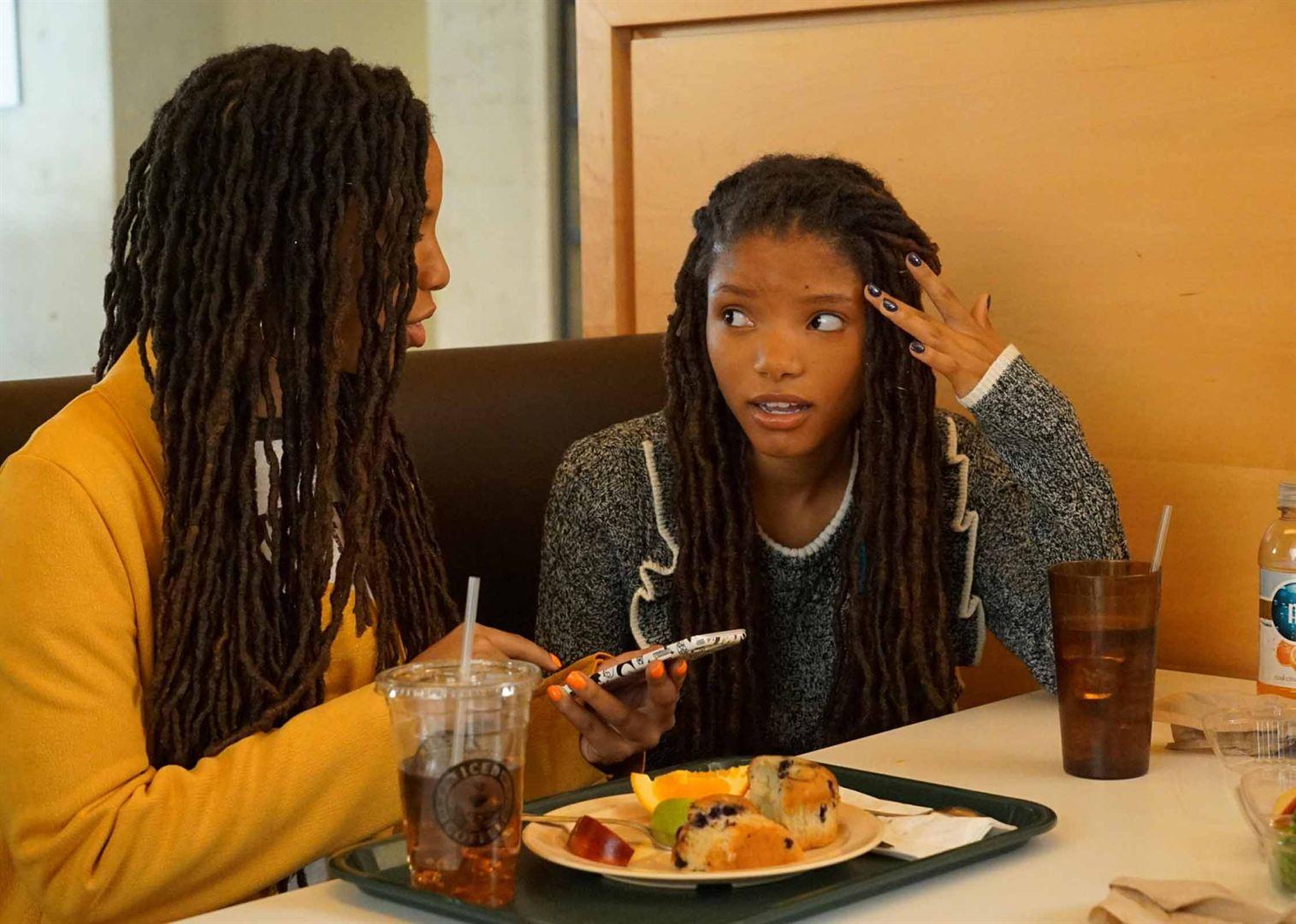 Cena de grown-ish. Nela estão duas meninas negras de cabelo longo. A da direita veste uma blusa cinza e olha para a outra com uma expressão de descrença. A da esquerda está de costas, sendo possível ver apenas sua blusa amarela. Ela segura um celular na mão, por cima de um prato de comida encostado na mesa na frente das garotas.
