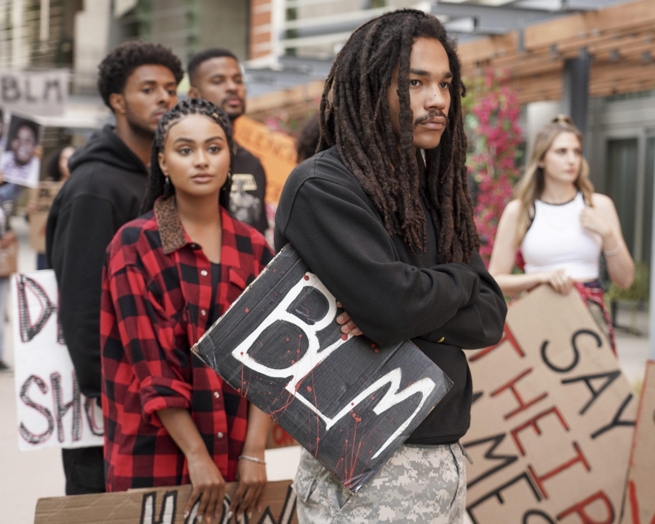"""Cena de grown-ish. Nela está centralizado um garoto negro, de cabelo em dreads, usando um moletom preto. Ele tem os braços cruzados e segura uma placa preta com """"BLM"""" escrito dentro, na cor branca. Atrás, em uma imagem embaçada, é possível ver outros protestantes segurando também placas."""