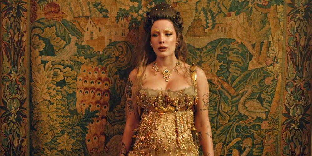 Sobre um papel de parede amarelo, Halsey está de pé. Ela veste um vestido dourado e olha com tristeza para a esquerda. Seu cabelo castanho está preso pela metade para cima em um topete.