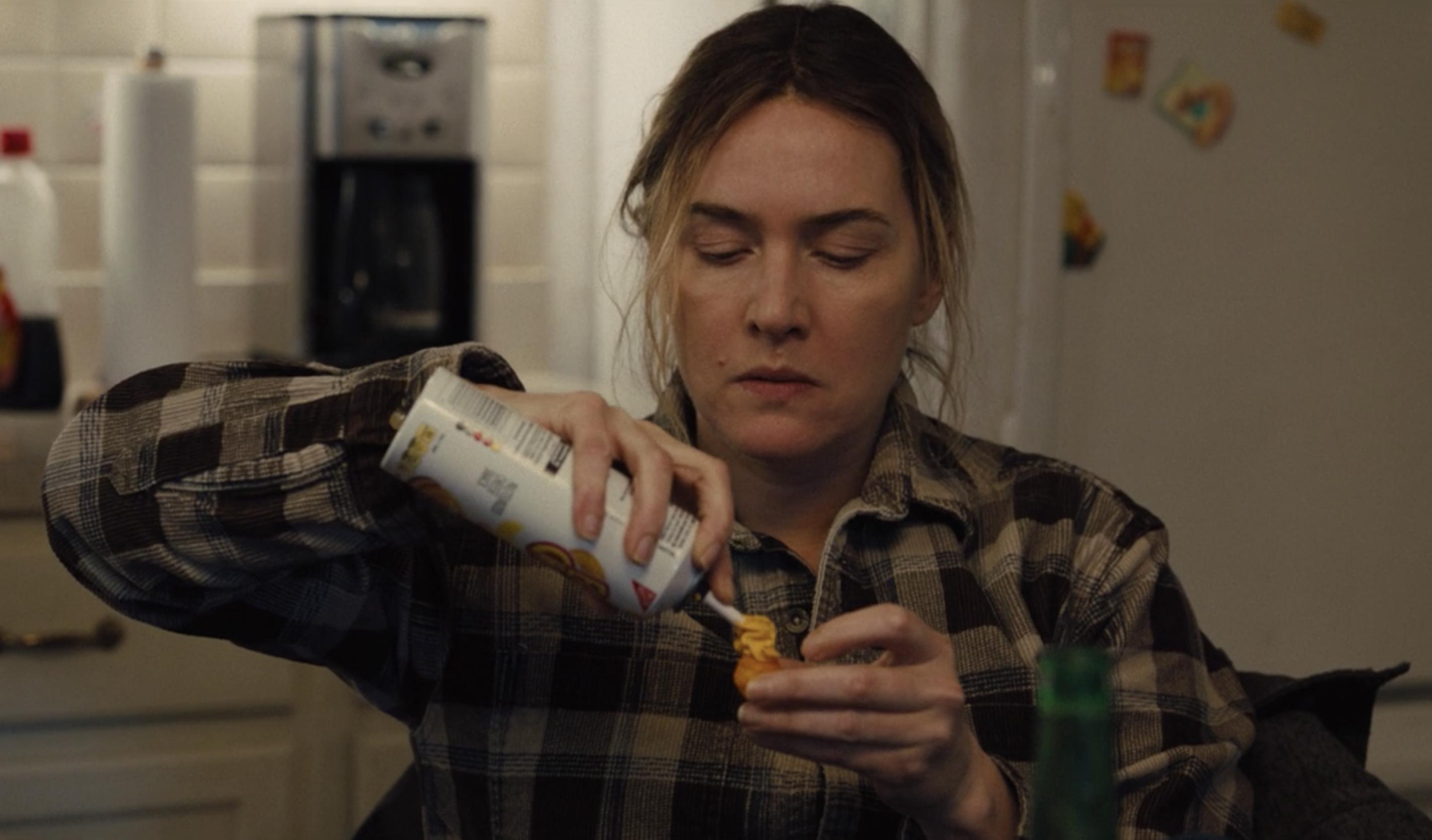 A imagem é uma cena da série Mare of Easttown. Nela, Kate Winslet, que interpreta Mare, está sentada na cozinha colocando queijo cheddar em um biscoito. Mare é uma mulher branca, de cabelos loiros presos em um coque baixo, ela veste uma camisa xadrez.