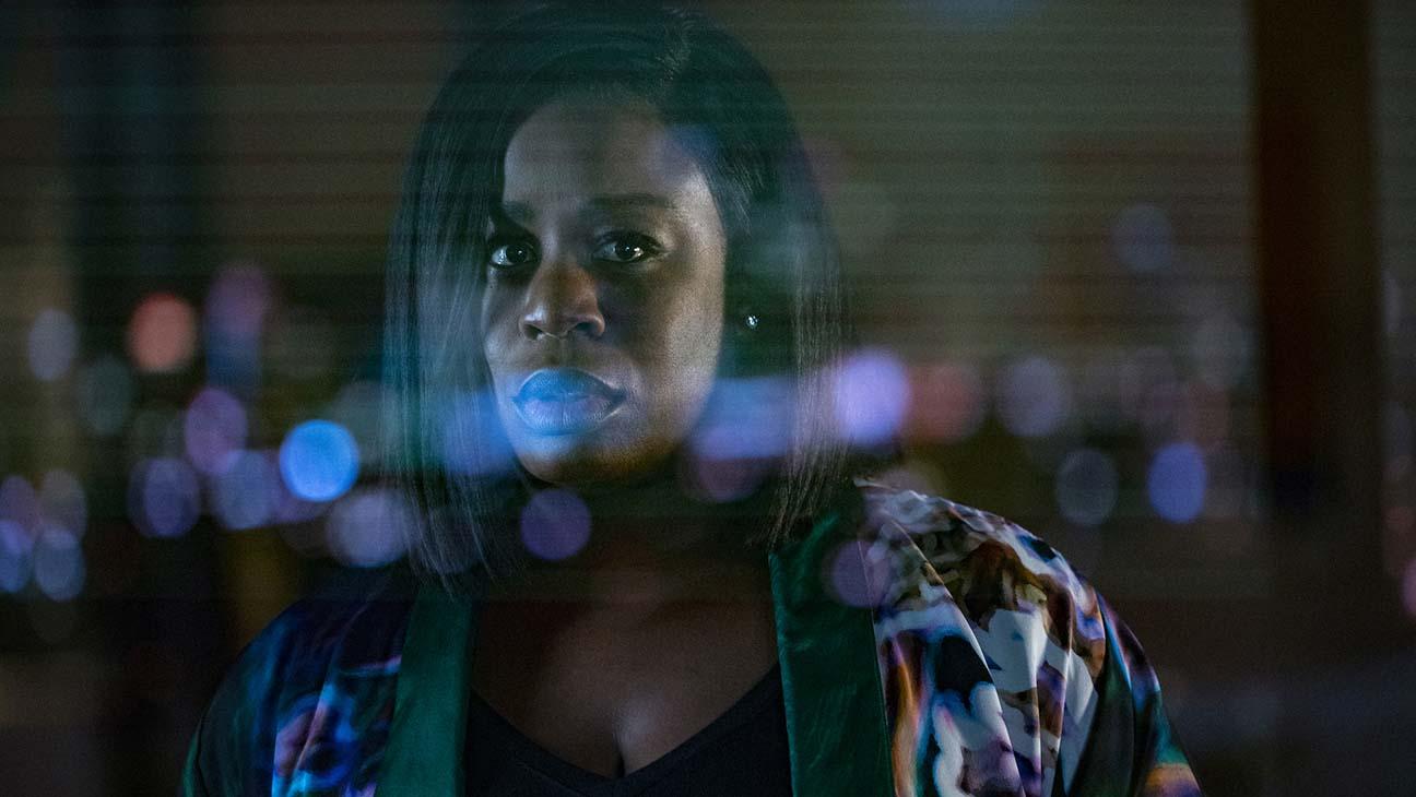 A imagem é uma cena da série In Treatment. Na imagem, Uzo Aduba, que interpreta Brooke Taylor, está atrás de uma porta de vidro, em que é possível ver reflexos de luzes da cidade. Brooke é uma mulher negra, de cabelos pretos, lisos e acima dos ombros; ela veste uma blusa preta e um kimono estampado. É possível ver dos seus seios para cima.