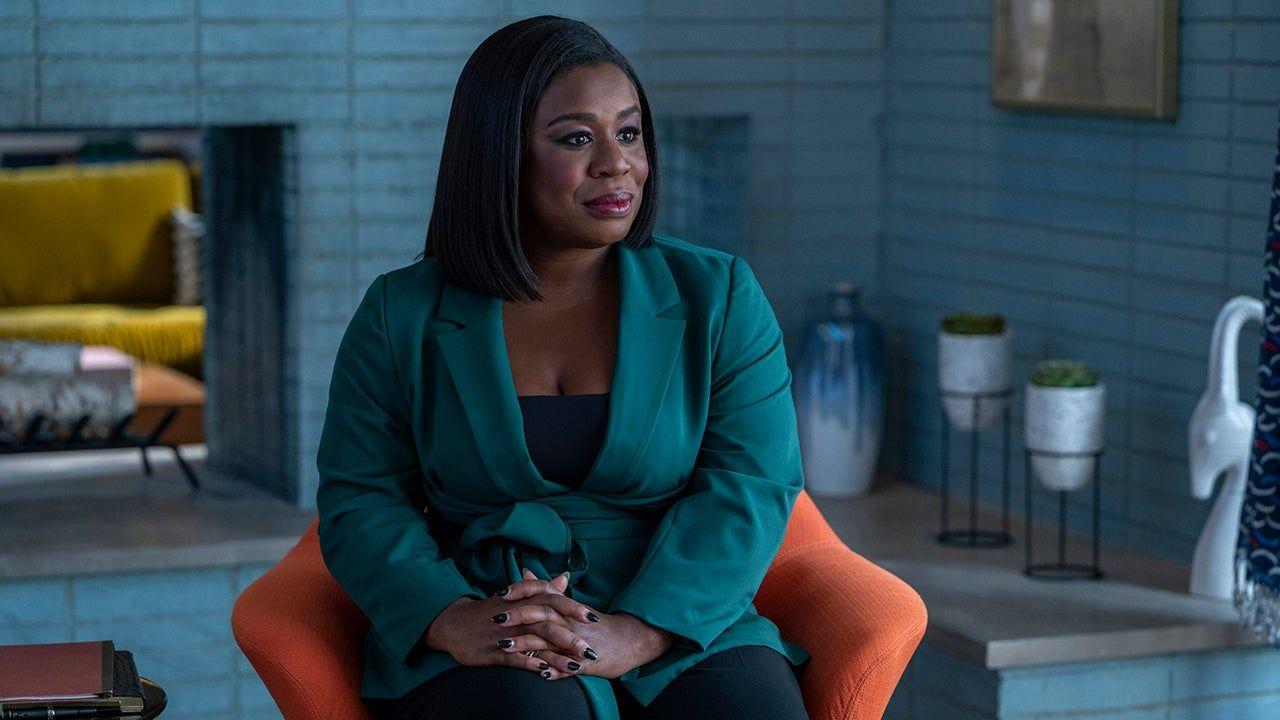 A imagem é uma cena da série In Treatment. Na imagem, Uzo Aduba, que interpreta Brooke Taylor, está sentada em uma poltrona laranja na sua sala de estar. Brooke é uma mulher negra, de cabelos pretos, lisos e acima dos ombros; ela veste uma blusa e calça pretas, e um blazer verde-marinho.