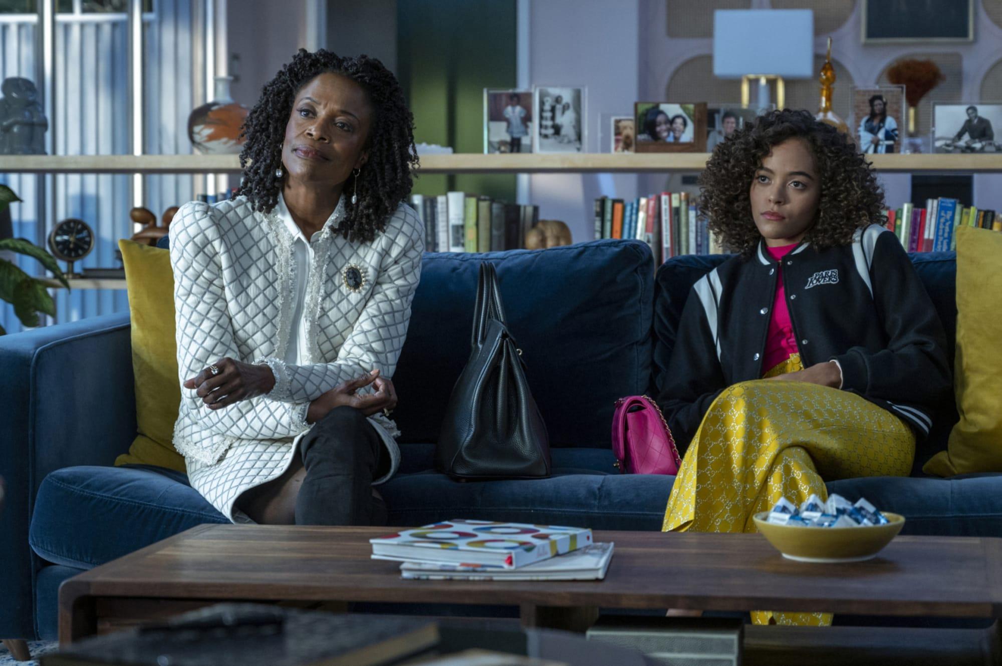 A imagem é uma cena da série In Treatment. Nela, Quintessa Swindelle, que interpreta Laila, está sentada no lado esquerdo de um sofá em uma sala de estar, ao lado direito está Charlayne Woodard, que interpreta Rhonda. Laila é uma jovem negra de pele clara, com cabelos cacheados e acima dos ombros; ela veste uma blusa rosa, um moletom preto estilo college e calças amarelas. Rhonda é uma senhora negra, de cabelos pretos cacheados na altura nos ombros, ela veste um conjunto de saia e blazer brancos.