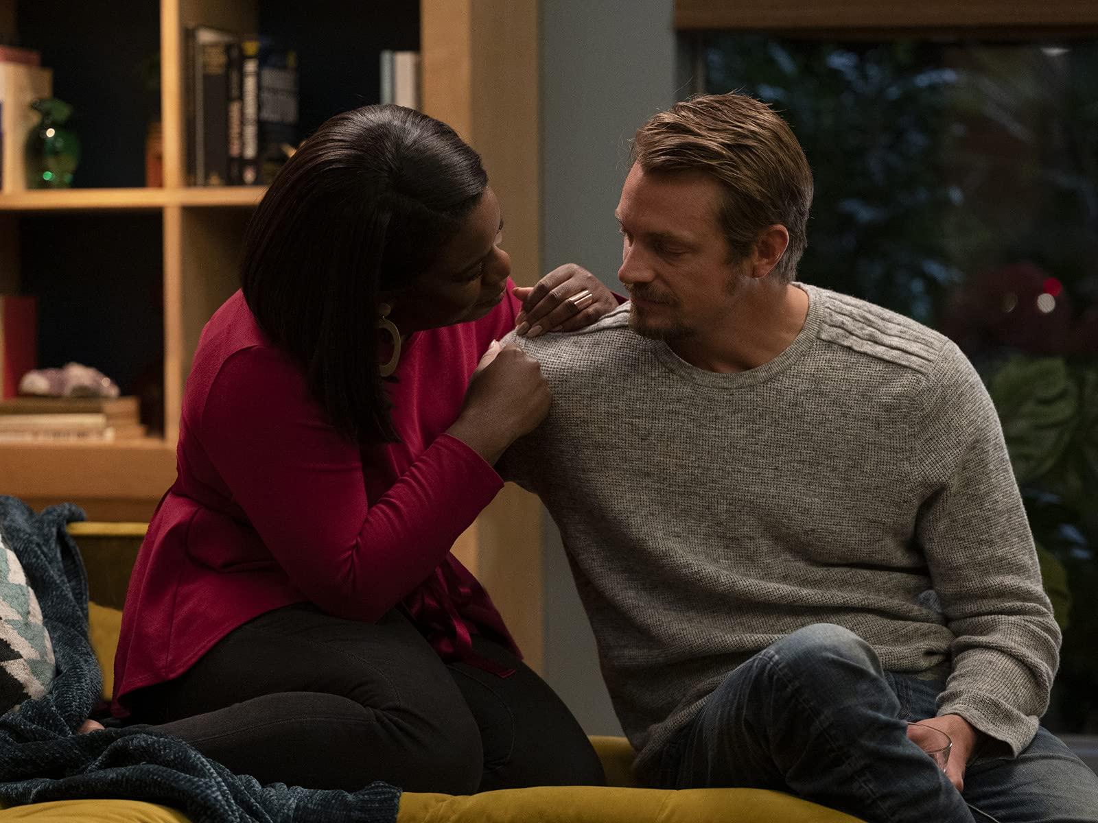A imagem é uma cena da série In Treatment. Na imagem, Uzo Aduba, que interpreta Brooke Taylor, está sentada ao lado de Joel Kinnaman, que interpreta Adam, apoiada em seu ombro direito. Brooke é uma mulher negra, de cabelos pretos, lisos e acima dos ombros; ela veste uma blusa rosa de mangas compridas e uma calça jeans escura. Adam é um homem branco, de cabelo e barba loiros; ele veste uma blusa cinza de mangas compridas e calça jeans.