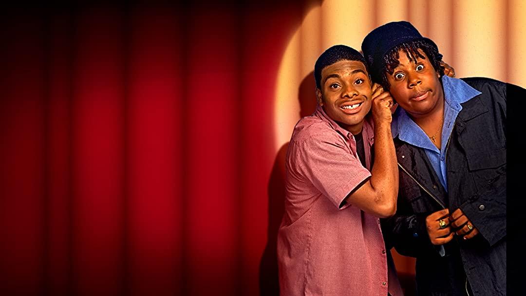 Foto da série Kenan e Kel. Kel está a esquerda, é um homem negro de cabelo bem rente e usa uma camisa flanelada rosa. Ao seu lado está Kenan, um homem negro de cabelos enrolados qhe usa um chapéu azul e jaqueta preta. Kel segura as orelhas de Kenan e, ao fundo, podemos ver uma cortina vermelha de teatro.