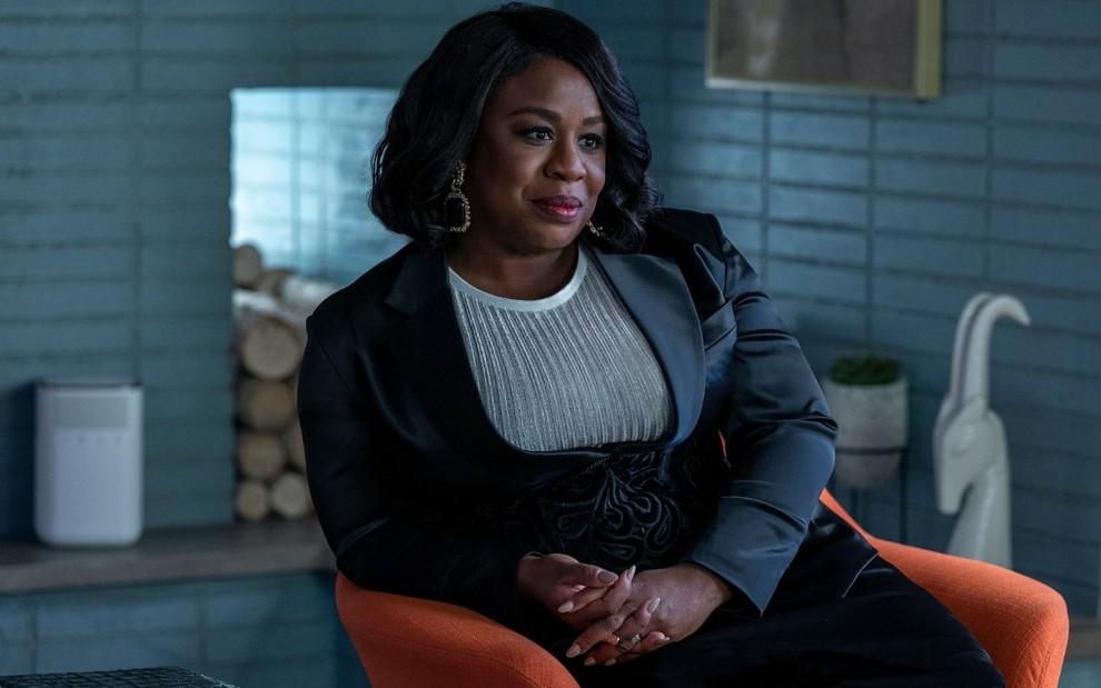 A imagem é uma cena da série In Treatment. Nela, Uzo Aduba, que interpreta a Dra. Brooke Taylor, está sentada em uma poltrona laranja em seu consultório. Uzo é uma mulher negra, de cabelos lisos, pretos e curtos; ela veste uma blusa branca, com um terno e saia verde-marinho, e também usa um par de brincos com uma pedra grande.