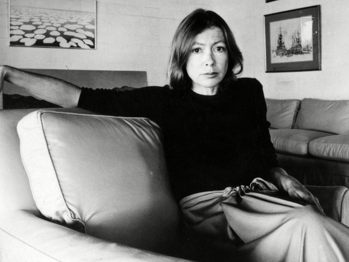 Fotografia da escritora Joan Didion. Na imagem, a mulher está posando sentada em um sofá, ela possui seu braço esquerdo acima do sofá e o braço direito sobre as pernas. A autora é uma mulher branca, de cabelos curtos castanhos e olhos escuros. Ela veste uma blusa cacharrel preta e uma calça clara.