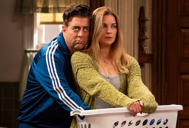 Cena da série Kevin Can F**k Himself. A cena mostra Kevin, branco, de moletom azul, abraçando sua esposa Allison, por trás, ela é loira, branca, usa roupa verde e segura um cesto de roupas que é de cor branca.