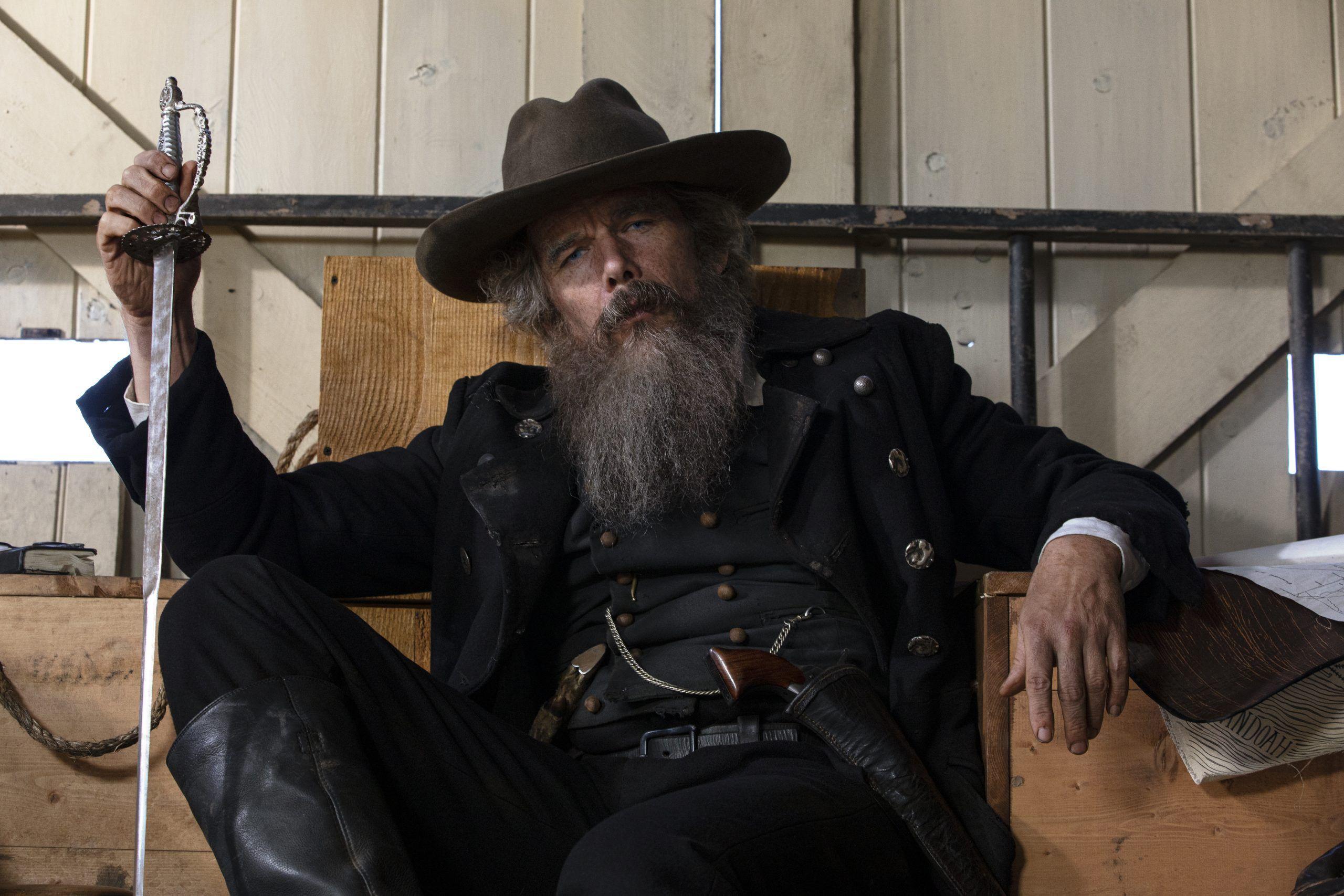 Cena da minissérie The Good Lord Bird. A cena mostra o personagem principal, interpretado por Ethan Hawke, sentado em uma cadeira, com uma espada na mão esquerda. Ele usa chapéu escuro, tem uma barba gigante e cinza e não tem uma aparência limpa