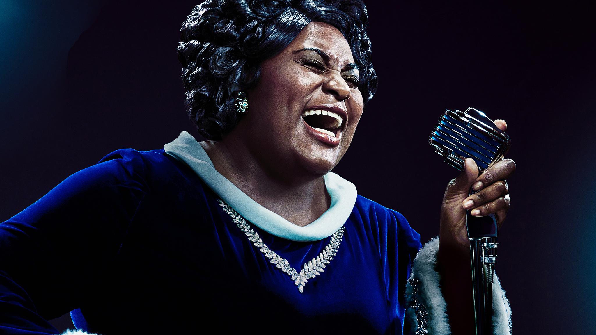Poster do filme Robin Roberts Presents: Mahalia. A foto mostra Mahalia cantando. Ela é interpretada por Danielle Brooks, uma mulher negra, gorda, que usa roupa azul e colar de brilhantes. Ela canta de olhos fechados, boca aberta e segurando o microfone com força