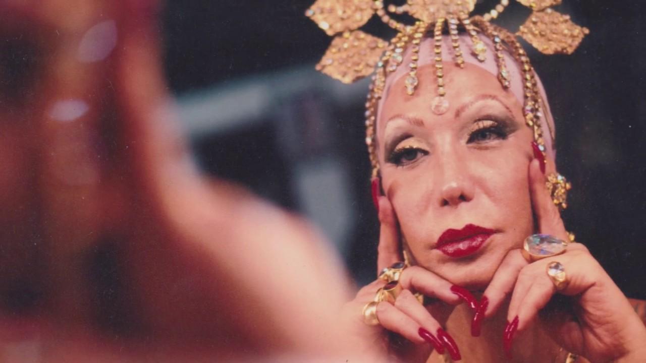 Foto em paisagem de Luana Muniz. Luana é uma mulher branca, de 56 anos, que usa um acessório como uma coroa dourada na cabeça. Ela está de frente ao espelho, mas só podemos ver seu reflexo, já que sua forma está borrada. Ela se encara com as mãos apoiadas no queixo. Luana usa esmalte vermelho, batom vermelho e sombra dourada, que combina com os anéis em seus dedos.
