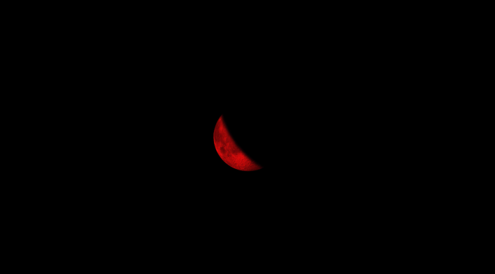 Imagem do documentário Meia lua Falciforme. No centro da imagem está apenas uma meia lua crescente colorida em vermelho e todo o fundo é preto.