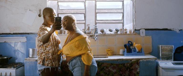 Cena de Minha história é outra.Uma mulher negra de cabelo raspado loiro vestindo shorts jeans e blusa estampada está tirando uma selfie com outra mulher negra de cabelo descolorido shorts jeans e camisa amarela amarrada na frente. Ambas estão de pé em uma cozinha azul clara.