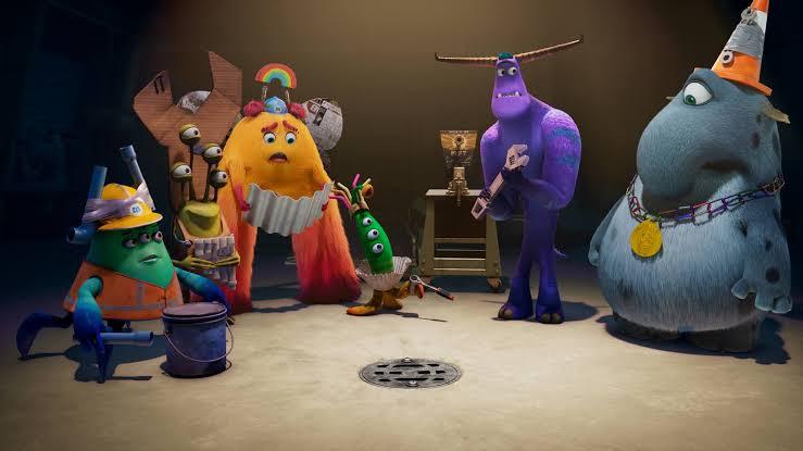 Cena de Monstros no Trabalho mostra seis monstros reunidos ao redor de um ralo com olhar de preocupação. Apenas um deles demonstra estar feliz com a situação.