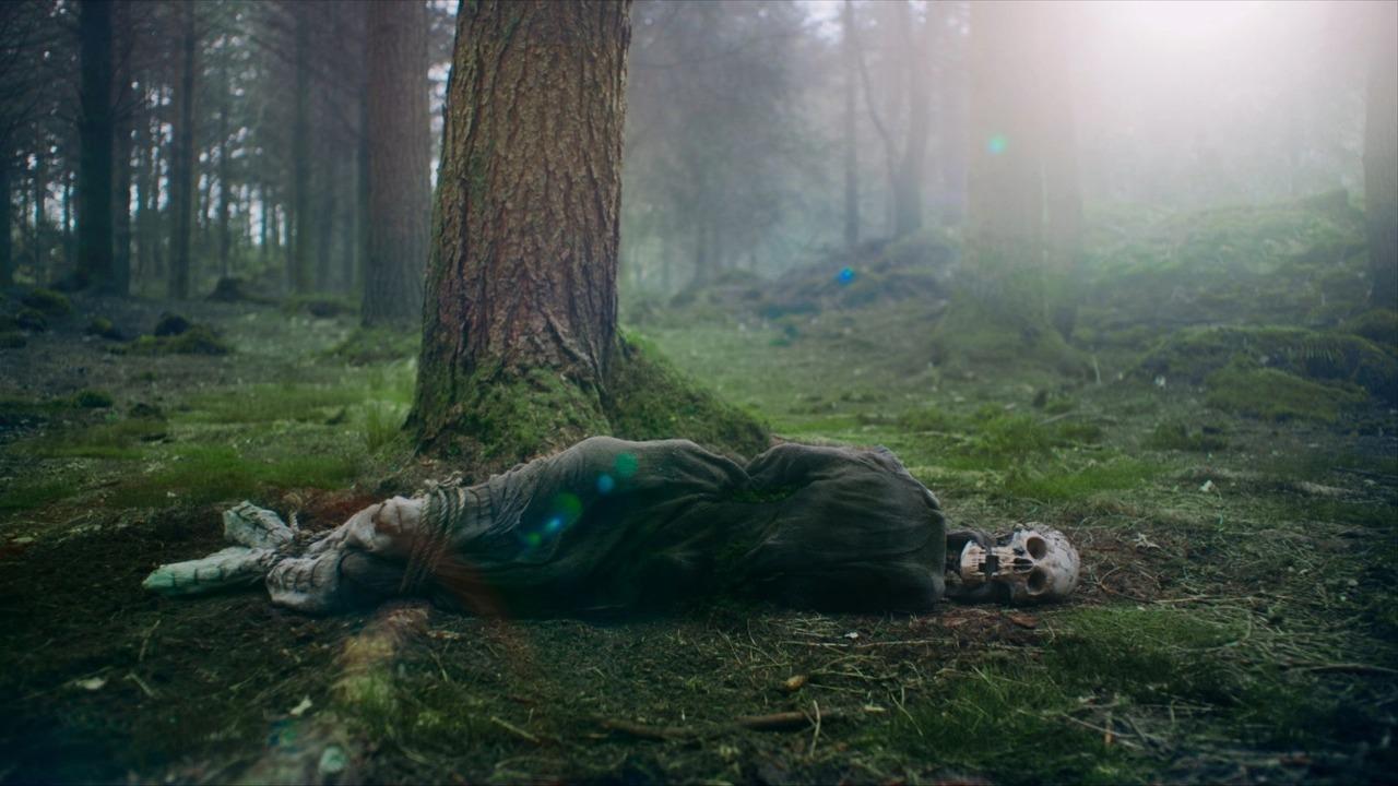 Cena do filme A Lenda do Cavaleiro Verde. Um esqueleto amordaçado jaz no chão verdejante de uma floresta. O esqueleto está com a cabeça à direita, virada para a direção da câmera, com os braços atrás de si e uma corda amarrando suas botas brancas. O resto de seu corpo é coberto por uma túnica cinzenta. Dentro de sua boca, um lenço que o amordaçava agora está solto. Faltam alguns dentes na mandíbula. Atrás dele, uma floresta se estende, com árvores retas e altas. Do canto superior direito da tela, a luz do Sol surge e ofusca parte da cena.