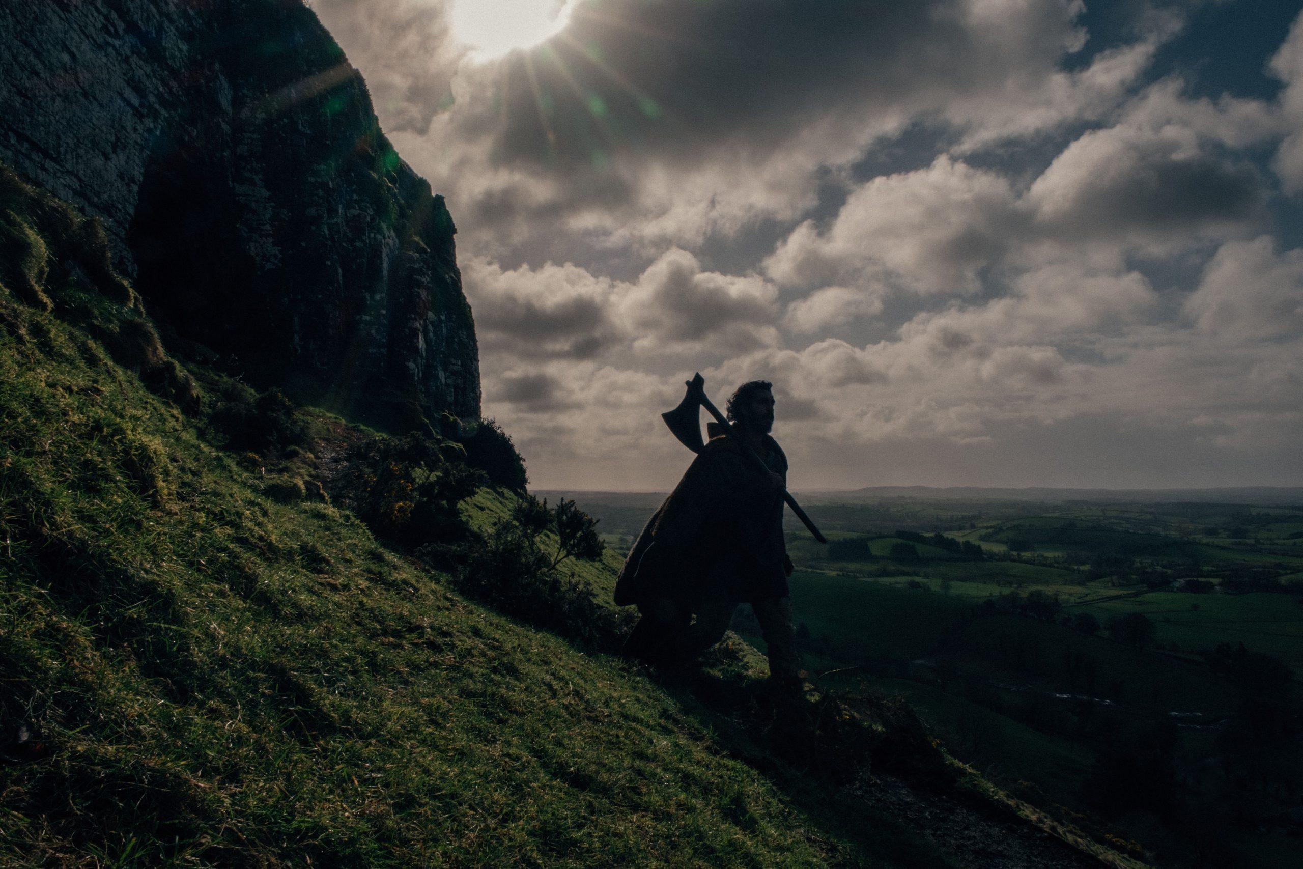 Cena do filme A Lenda do Cavaleiro Verde. Gawain (Dev Patel) caminhando pela encosta de uma montanha. Gawain é indiano, mas vemos apenas sua silhueta sombreada, com o brilho do Sol no alto em algum ponto à esquerda dele. Vemos que ele tem cabelos um pouco longos, usa um tipo de capa e carrega um grande machado apoiado no ombro direito, com a lâmina virada para o chão. Ele caminha da esquerda para a direita, com a montanha às suas costas e uma vasta planície verdejante no fundo da cena. Ele caminha em cima da grama e o céu acima de si é ensolarado com diversas nuvens.