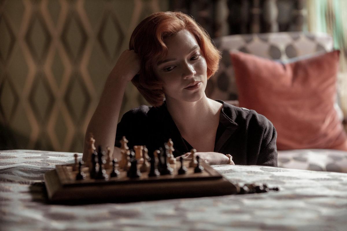 A imagem é uma cena da série O Gambito da Rainha. Nela, a atriz Anya Taylor-Joy, que interpreta Beth Harmon, está sentada ao lado de uma cama, com sua cabeça apoiada na mão direita, olhando para um tabuleiro com peças de xadrez em cima da cama. Ela é uma mulher branca, de cabelos ruivos acima dos ombros, e é possível ver que ela veste um casaco marrom escuro