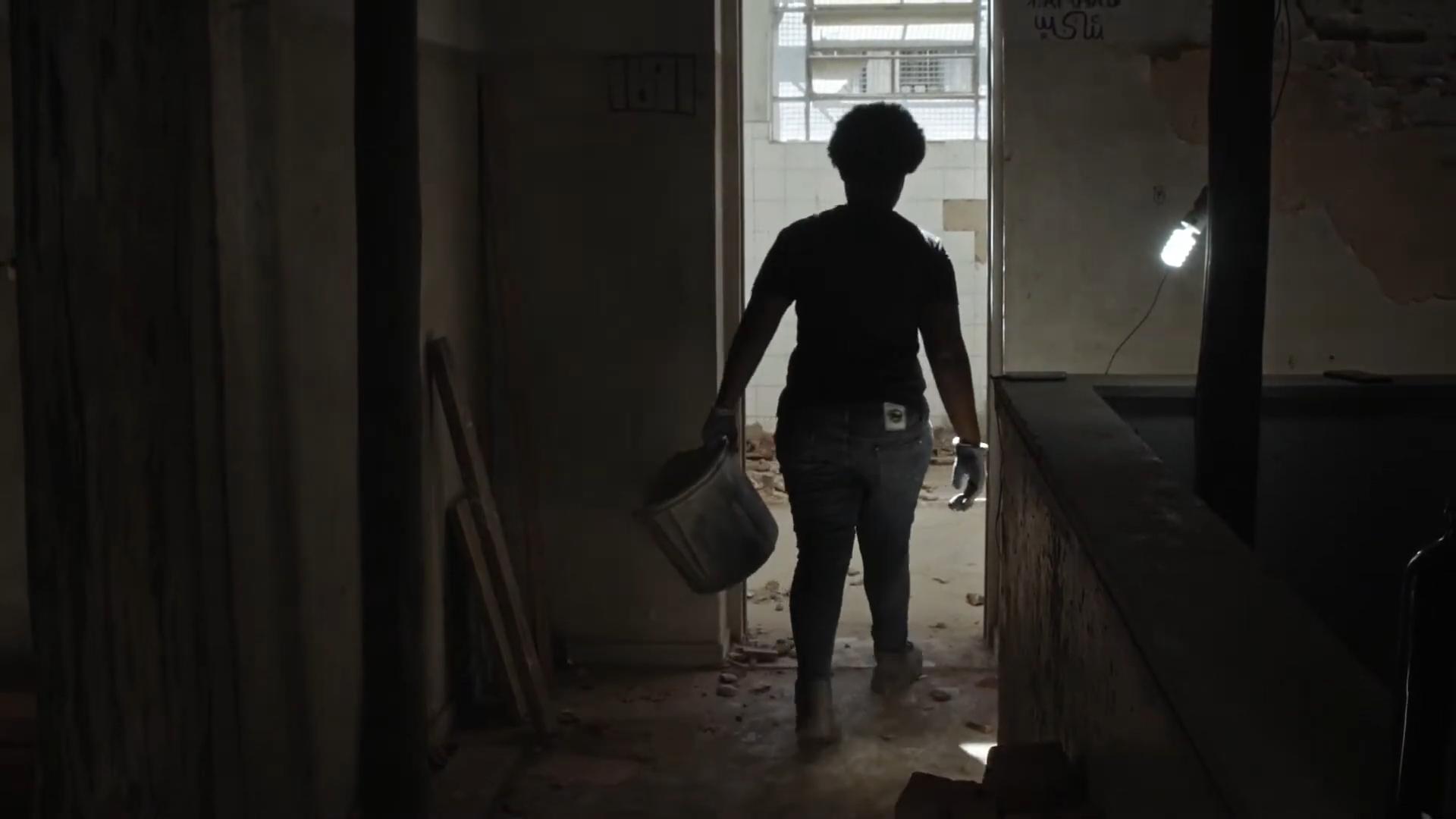 Cena do curta Obreiras. Fotografia em paisagem. Imagem de um canteiro de obras escuro. A única fonte de luz é uma porta, que abre para um espaço claro, e uma lâmpada acesa no escuro. Uma das protagonistas anda pela porta, segurando um balde.