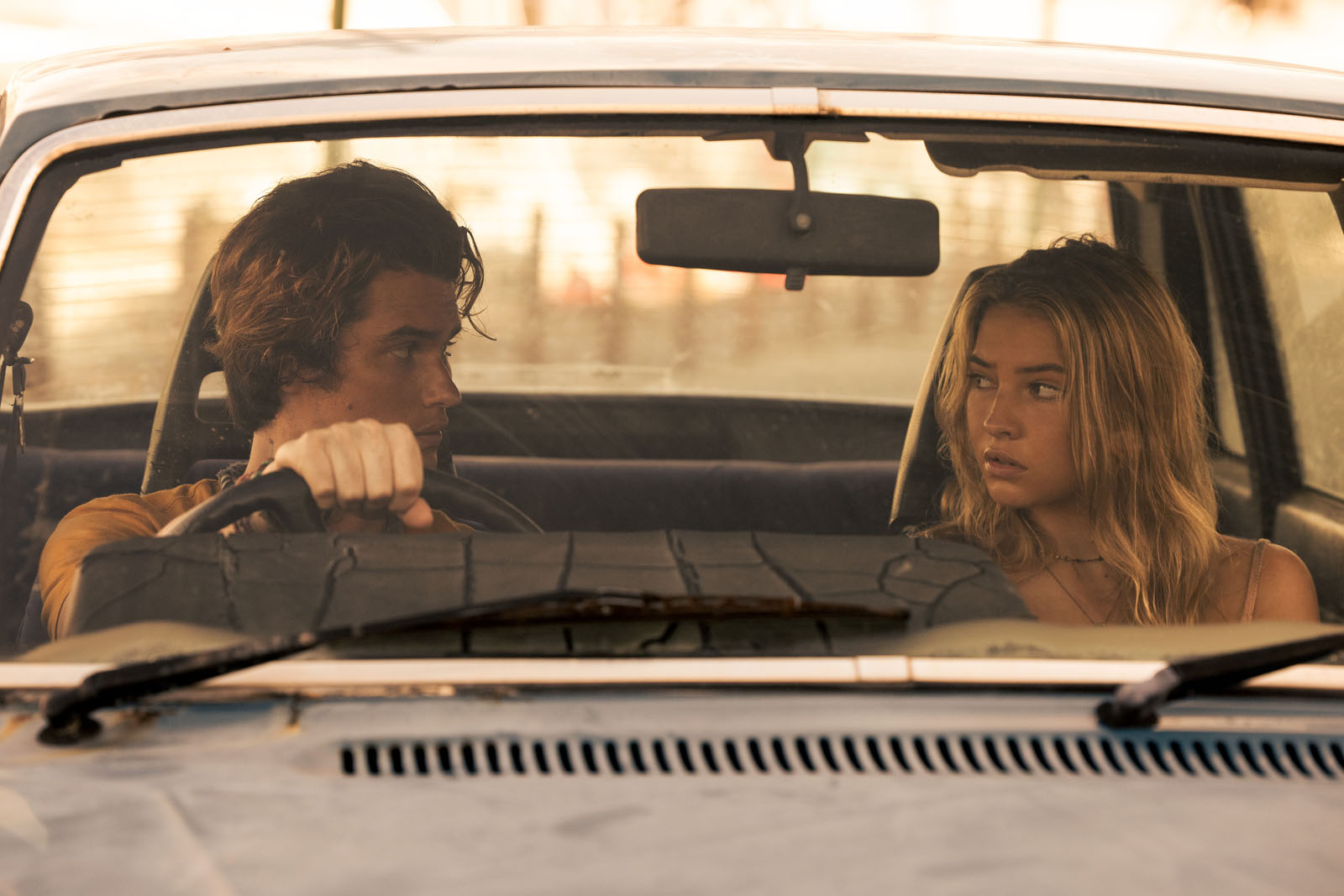 Foto de Sarah e John B. A menina é branca de cabelo loiro. Ela está sentada na direita do carro, olhando para o menino ao seu lado. Este é também branco e de cabelo loiro escuro. Sua blusa é amarela. O carro em que se encontram é cinza escuro.