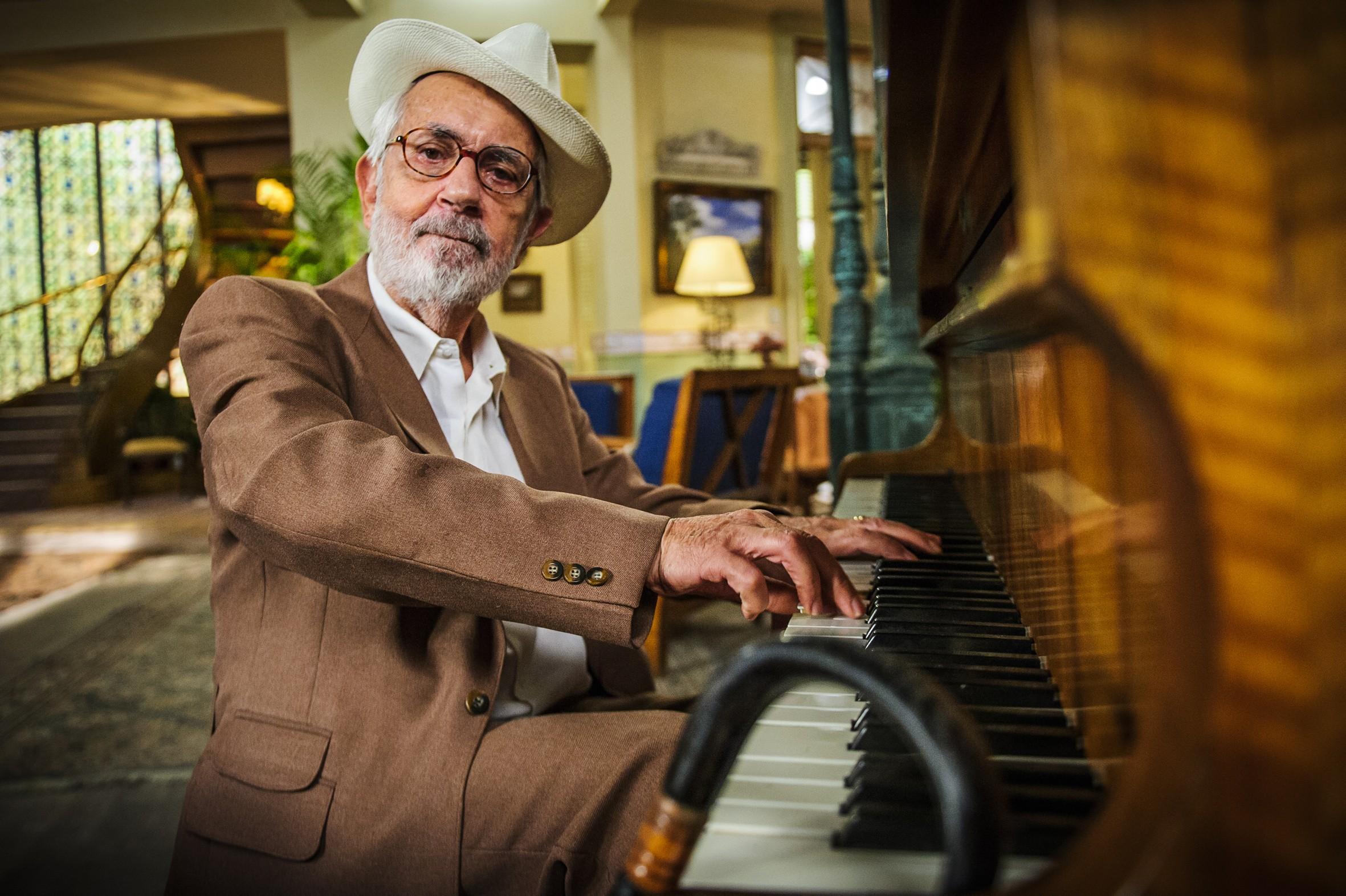 A imagem é uma fotografia do ator Paulo José tocando piano. Paulo é um senhor branco, de barba e cabelos grisalhos, ele veste uma camisa branca, um terno e calça social em tom marrom claro, e também usa um óculos de grau e um chapéu branco.