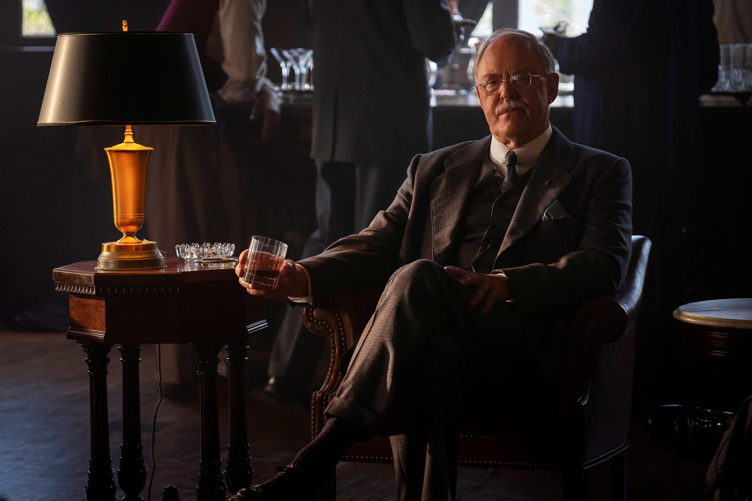Cena da primeira temporada de Perry Mason. E.B. Jonathan (John Lithgow) está sentado numa cadeira acolchoada, com um copo de bebida na mão, olhando para frente, de pernas cruzadas. E.B. é um homem caucasiano velho de cabelos brancos e ralos, com bigode branco e óculos finos. Seu terno é cinza escuro, com uma camisa branca por baixo, uma gravata azul e um lenço azul no bolso do paletó. À direita dele, uma mesa de centro com um abajur e um cinzeiro de cristal vazio. O chão é de madeira e, atrás de E.B., três homens no balcão de um bar conversam e bebem de pé. Atrás do balcão, uma janela aberta ilumina a cena.