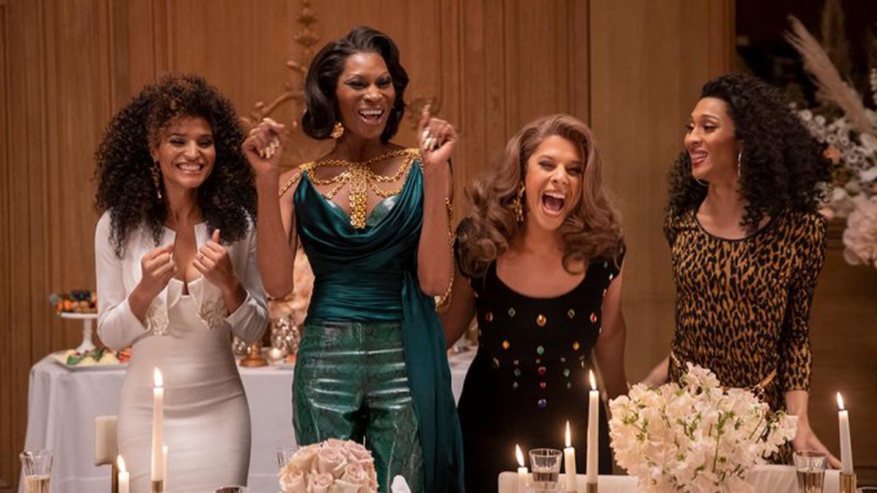 Cena da série Pose. A cena mostra 4 mulheres negras, em pé e sorrindo, uma ao lado da outra, usando roupas chiques. Á direita, está Angel, de vestido branco; Elektra, de roupa verde; Lulu, de roupa preta; e Blanca, usando vestido com estampa de oncinha.