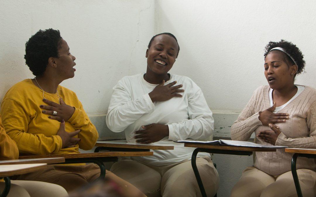 Cena do curta Quando elas cantam. A cena mostra 3 mulheres negras, sentados em carteiras escolares, cantando sorrindo, olhando umas para as outras.